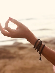 hand in mudra pose with mala